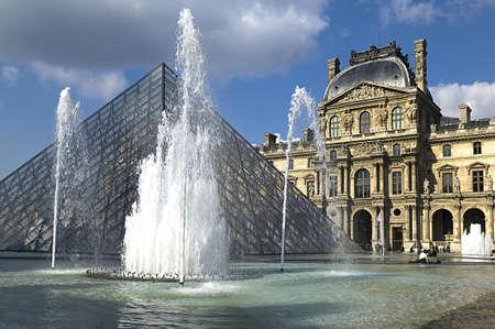 piramide humana: PARÍS - 15 de marzo de 2010. Pirámide de cristal y la fuente en el Museo del Louvre. El museo fue inaugurado en 1739