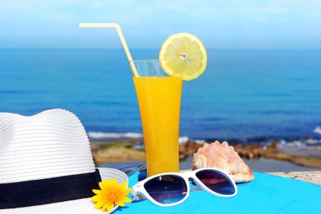 yellow fruit cocktail and a white hat on the background of a beautiful sea landscape Stock Photo - 14132089