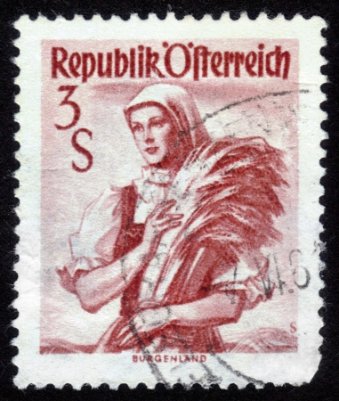 AUSTRIA - CIRCA 1949  A stamp printed in Austria shows a woman in the Austrian national dress , inscription  Burgenland  from the series  Costumes , circa 1949 Stock Photo - 14132091