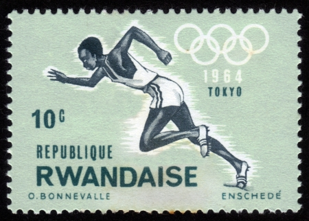 summer olympics: RWANDA - CIRCA 1964: A stamp printed in Rwanda shows a black runner at the Summer Olympics in Tokyo in 1964, circa 1964