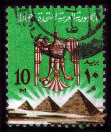 EGYPT - CIRCA 1971  stamp printed by Egypt, shows Eagle, coat of arms of Egypt, against the background of the pyramids, circa 1971 Stock Photo - 14388401