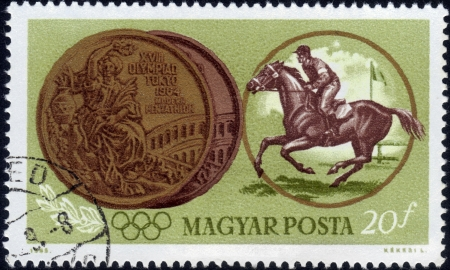 HUNGARY - CIRCA 1965  A stamp printed in Hungary shows jockey riding horse and Olympic medal, devoted to Olympic games in Tokyo, circa 1965 Stock Photo - 14376593