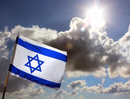israeli: Bandera de Israel en el fondo de cielo nublado alarmante