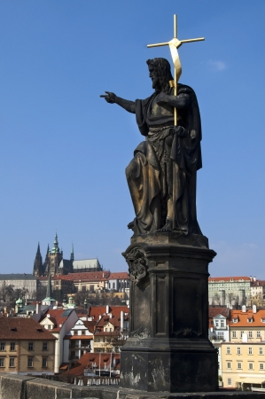 Statue on Charles Bridge on the background of the Prague Castle , Prague , Czech republic photo