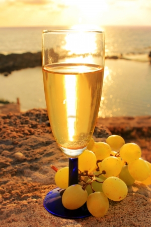 still life with glass of wine and grapes in the sunset at the beach Stock Photo - 14849076