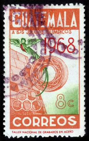 GUATEMALA - CIRCA 1968: A stamp printed in the Guatemala, shows Olympic symbols and the bird of Paradise, is dedicated to the Olympic Games in Mexico City, circa 1968 Stock Photo - 15438115