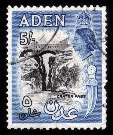 ADEN - CIRCA 1956: sello impreso en Aden muestra paso cráter y la imagen de la reina británica Isabel. Aden se convirtió en una colonia de la Corona del Reino Unido en 1954. Circa 1956