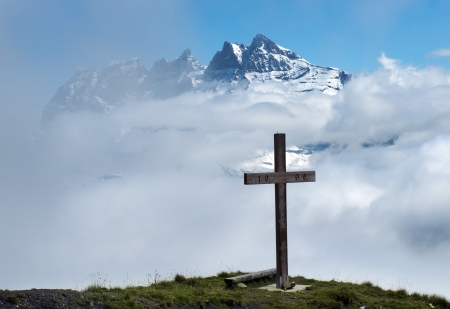 wooden cross in the clouds on a background of snowy peaks in the Swiss Alps photo