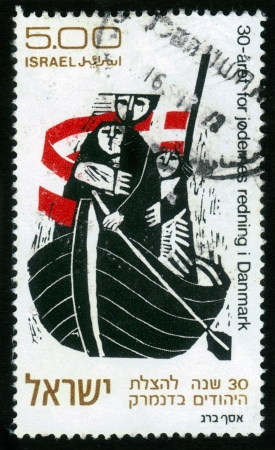 Israel - CIRCA 1973: A stamp printed in Israel shows Jewish refugees in the boat, the flag of Denmark , devoted 30th anniversary of the rescue of Danish Jews , circa 1973 photo