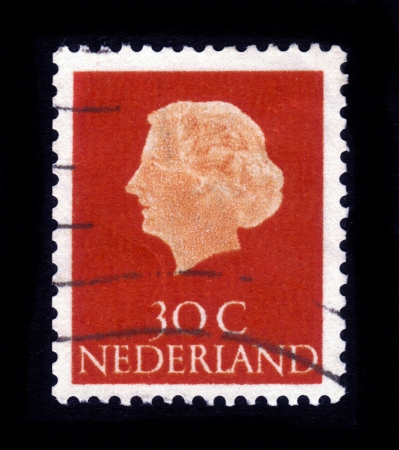 regnant: NETHERLANDS - CIRCA 1953: A stamp printed in Netherlands shows portrait of Queen regnant of Netherlands Juliana Louise Emma Marie Wilhelmina on a terracotta  background ,circa 1953 Editorial
