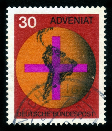 GERMANY - CIRCA 1969: A stamp printed in Germany shows emblem of ADVENIAT charitable organization of German Catholics, Globe with a focus on Central and South America, before a Christian cross , circa 1969 Stock Photo - 15987084
