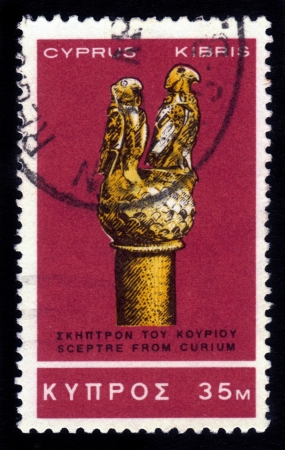 surmounted: CYPRUS - CIRCA 1966: A stamp printed in Cyprus shows gold sceptre from Curium,surmounted by a sphere on top of which stand two hawks. 11th century B.C. (Cyprus Museum) , circa 1966