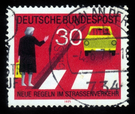 GDR (EAST GERMANY) - CIRCA 1971: a stamp printed in GDR (East Germany) shows woman at a pedestrian crossing and car , devoted to the explaining rules of the road,  series Road safety, circa 1971 Stock Photo - 16007416