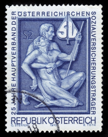 low relief: AUSTRIA - CIRCA 1973: A stamp printed in Austria shows two men supporting each other , devoted  to 25 years Main Association of Austrian Social Security Institutions, circa 1973.