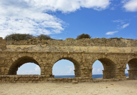 stone arches of ancient Roman aqueduct at Caesarea along the coast of the Mediterranean Sea, Israel  Stock Photo