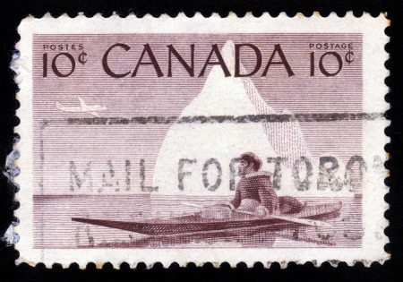 CANADA - CIRCA 1955  stamp printed by Canada, shows Eskimo on a kayak against the background an iceberg, circa 1955 Stock Photo - 16126428