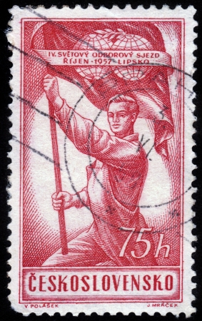 CZECHOSLOVAKIA - CIRCA 1957: A stamp printed in Czechoslovakia, shows a young worker holding a red flag , devoted to the IV World Congress of Trade Unions , circa 1957 Stock Photo - 16233029