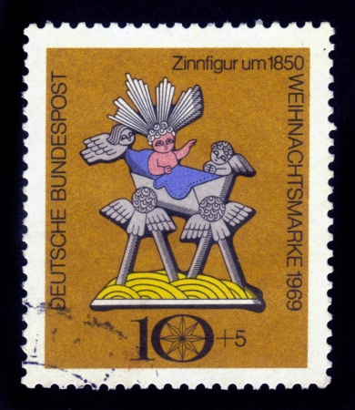 Germany - CIRCA 1969  a stamp from Germany shows pewter figurine depicting a baby in a crib and the angels, Christmas tale, circa 1969 Stock Photo - 16540619