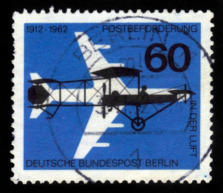 GERMANY - CIRCA 1962  A stamp printed in the Germany shows silhouette a four-engine jet plane and vintage airplane   yellow dog   of 1912, circa 1962 photo