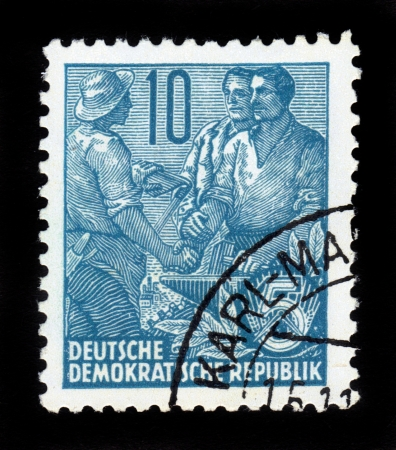 DDR - CIRCA 1958  A stamp printed in GDR  German Democratic Republic - East Germany  shows farmer shakes hands two workers , series   workers for the five year plan  , circa 1958 Stock Photo - 16585812