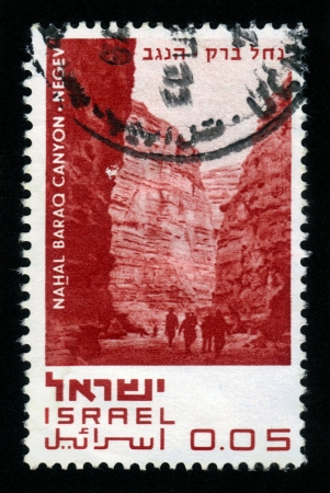 ISRAEL - CIRCA 1970  a stamp printed in the Israel shows tourists walking on the bottom of the mountain canyon Nahal Baraq , series  Nature Reserves of Israel  with inscription  Nahal Baraq Canyon - Negev ; series, circa 1970 Stock Photo - 16680137