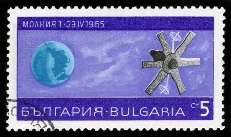 BULGARIA - CIRCA 1965  A stamp printed in Bulgaria shows Earth and Soviet satellite   molnia 1  , Lightning 1 , circa 1965 Stock Photo - 16878673