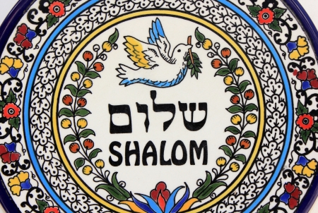 decorative plate with the image of a dove carrying an olive branch and inscription peace in Hebrew and English Stock Photo