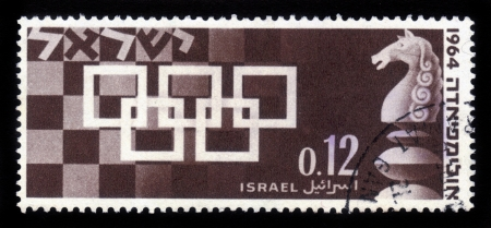 ISRAEL - CIRCA 1964  A stamp printed in Israel, shows the symbol of the chess  games held in Tel-Aviv 1964, with a chess-board in the background and pieces of the game, circa 1964 Stock Photo - 16978772