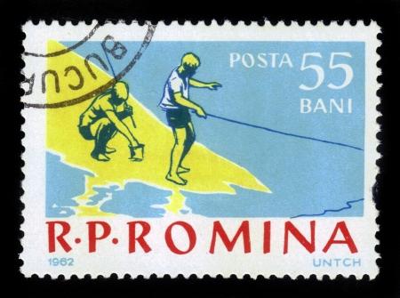 ROMANIA - CIRCA 1962: A stamp printed in the Romania shows boys on a fishing trip, circa 1962. Stock Photo - 17019587