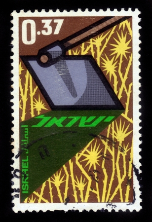 ISRAEL - CIRCA 1963: A stamp printed in Israel, shows a hoe clearing a field of thistles,  in honor of Year of the Pioneers, circa 1963 Stock Photo - 17377573