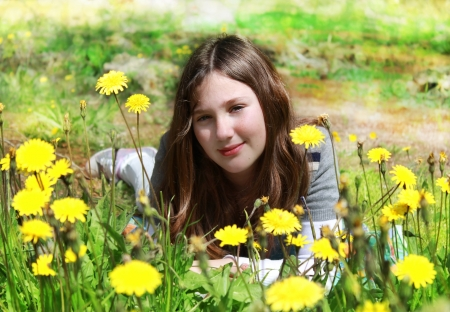young girl smiling dreamily among yellow flowers photo