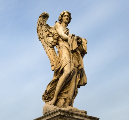 statue of an angel standing on the bridge leading to the Castle Sant Angelo, Rome