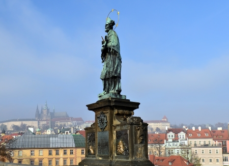 Statue  Saint on Charles Bridge on the background of medieval Prague, Czech republic photo