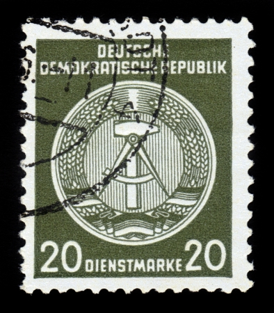GDR - CIRCA 1952  A Stamp printed in GDR  German Democratic Republic - East Germany  shows GDRs national coat of arms, caliper compasses and hammer, union of intellectuals and workers, green background, circa 1952 Stock Photo - 17757965