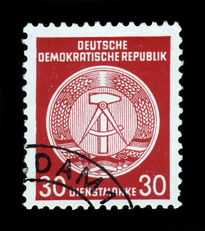 GDR - CIRCA 1952  A Stamp printed in GDR  German Democratic Republic - East Germany  shows GDRs national coat of arms, caliper compasses and hammer, union of intellectuals and workers, red background, circa 1952 Stock Photo - 17757963