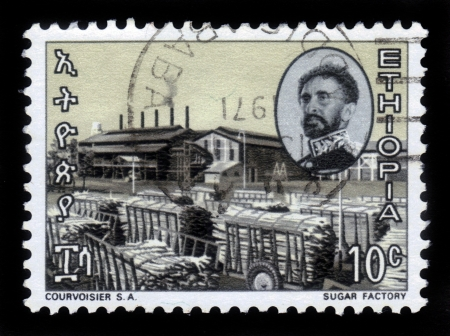 amharic: ETHIOPIA - CIRCA 1971   A stamp printed in Ethiopia shows portrait of emperor Haile Selassie and sugar factory , with the inscription in amharic , series, circa 1971 Editorial