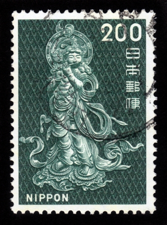 bodhisattva: JAPAN - CIRCA 1966  A post stamp printed in Japan shows Bodhisattva, who plays the flute, circa 1966 Stock Photo