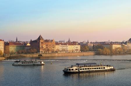 PRAGUE, Czech Republic - November 14 Tourists float on a boats on the Vltava river on the background a beautiful view over Prague on November 14, 2012 in Prague, Czech Republic Stock Photo - 18113859