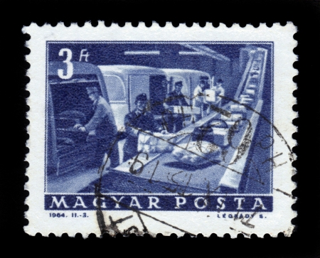 HUNGARY - CIRCA 1963:A stamp printed in Hungary shows postal employees and the conveyor to parcels, circa 1963. Stock Photo - 18401629