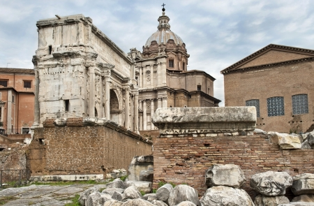 ruins of the Roman Forum, a triumphal arch and the Catholic church against cloudy sky photo