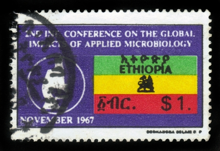 amharic: ETHIOPIA - CIRCA 1967   A stamp printed in Ethiopia national state flag of Ethiopia , with the inscription in amharic , devoted to the international conference on microbiology, circa 1967