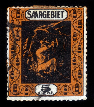 GERMANY - CIRCA 1934  a stamp printed in the territory of the Saar Basin was usually called the Saar or the German  Saargebiet, shows miner in the mine, circa 1934 Stock Photo - 19010088