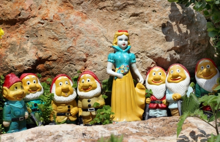 clay figurines of Snow White and the Seven Dwarves, standing between the stones
