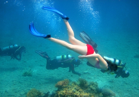 young girl in bikini swimming underwater on the background three divers