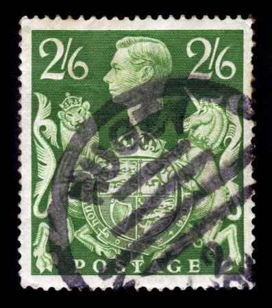 UNITED KINGDOM - CIRCA 1939 : a stamp printed in England, shows an  portrait of king George VI , lion and unicorn holding a royal coat of arms, circa 1939 Editorial
