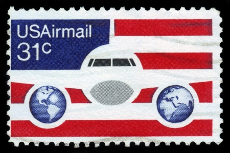united states postal service: UNITED STATES OF AMERICA - CIRCA 1976  a stamp printed in the USA shows image of an aeroplane, two hemispheres of the globe on the background of the American flag, circa 1976