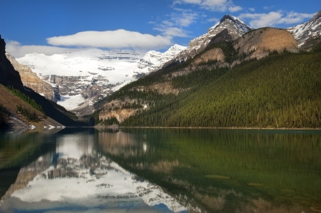 a reflection of the great Rocky Mountains in the waters of Lake Agnes, Banff Alberta, Canada photo