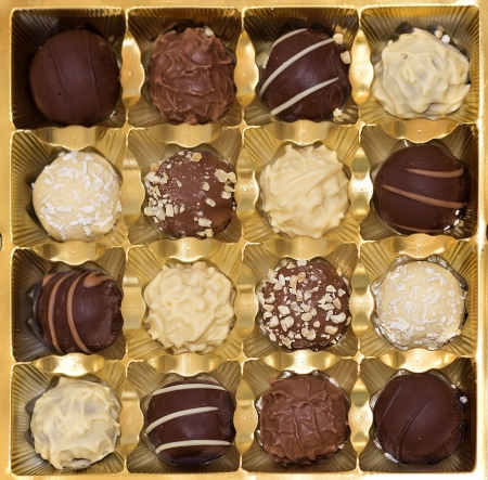 truffles of dark, milk, and white chocolates in a golden gift box photo