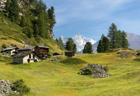 old stone and wooden small houses on the green slopes of the Swiss Alps in the background of snowy peaks photo
