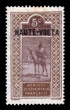 camel post: UPPER VOLTA, BURKINA FASO - CIRCA 1920  A stamp printed in France shows man with a spear on a camel, Issue of Afrique Occidentale Francaise with imprint  HAUTE-VOLTA , circa 1920